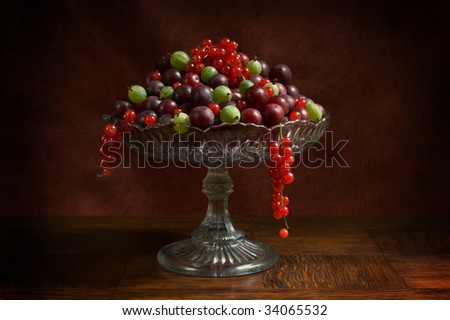 fruitbowl shot with soft light; contains plums, gooseberries and red berries - stock photo