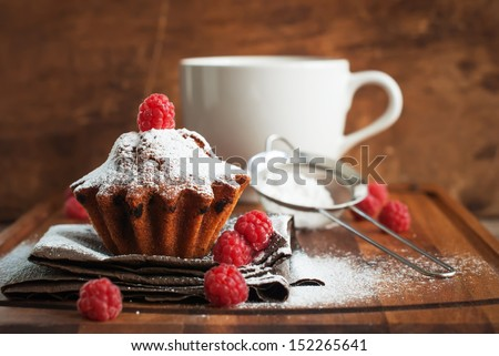 Fruitcake Decorated with Raspberry and icing sugar at the wooden table, horizontal - stock photo