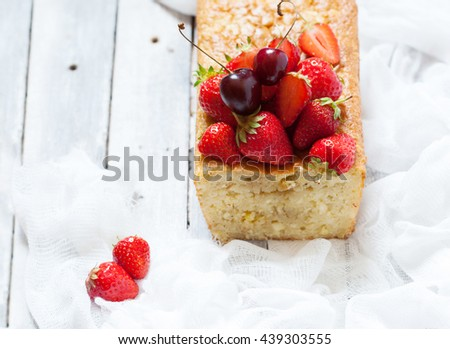 Fruitcake with strawberry and cherry topping on the old white wooden table, copy space