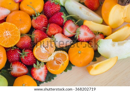 fruits and green leaves on wood texture : strawberry, orange, guava, peach