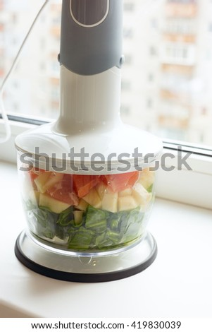 Fruits and herbs in a blender ready-to-cook of green cocktail.