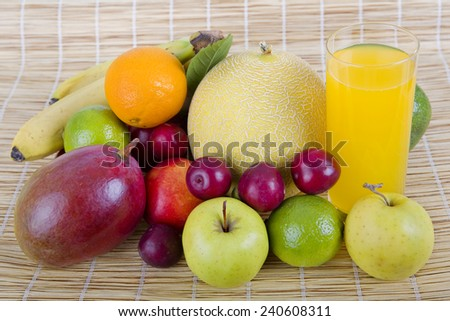 fruits and juice on wooden table - stock photo