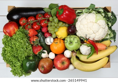 Fruits and vegetables like oranges, apple, tomatoes, banana in wooden box groceries from above