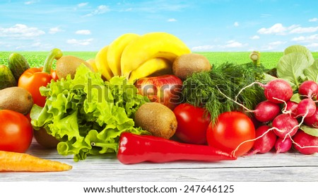Fruits and vegetables on wooden table and field with green grass on background - stock photo