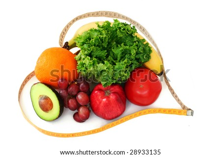 Fruits and vegetables surrounded by a heart shaped measuring tape on white background - stock photo