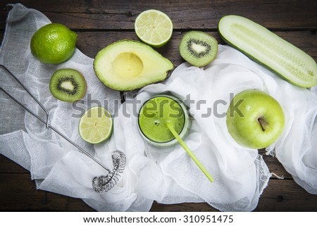 Fruits and vegetables with a glass of fresh green smoothie on a wooden table - stock photo