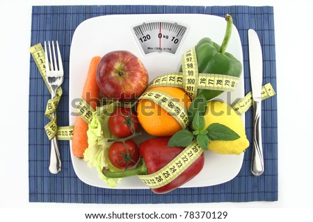 Fruits and vegetables with measuring tape on a plate as weight scale - stock photo