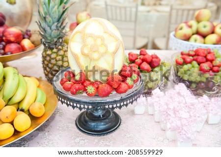 Fruits arrangement. Fresh various fruits elegant decoration. Assortment of exotic fruits. Multicolored fruits. Wedding decoration with fruits on restaurant table, pineapple, bananas, nectarines, kiwi - stock photo