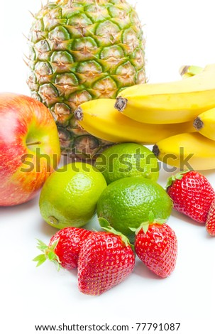 Fruits. Arrangement of various fresh ripe fruits: pineapple, bananas, apple, limes  and strawberries closeup  isolated on white background