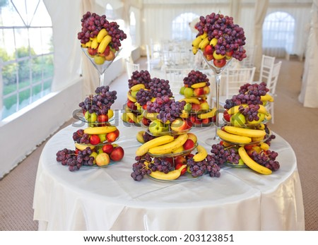 Fruits arrangement on restaurant table. Wedding decoration with fruits, bananas, grapes and apples.  - stock photo