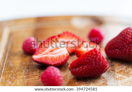 fruits, berries, diet, eco food and objects concept - close up of fresh ripe red strawberries on cutting board - stock photo