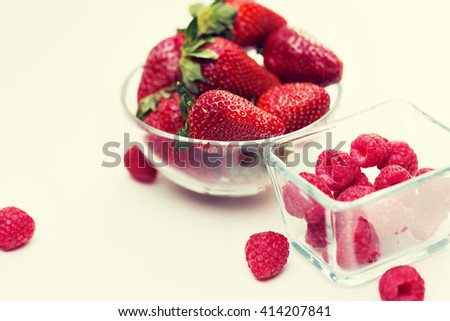 fruits, berries, diet, eco food and objects concept - close up of juicy fresh ripe red strawberries and raspberries in glass bowls over white - stock photo