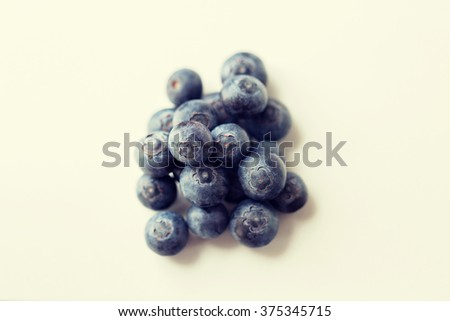 fruits, berries, diet, eco food and objects concept - juicy fresh ripe blueberries on white - stock photo