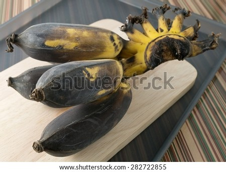 Fruits, Bunch of Black Rotten Wild Banana, Asian Banana or Cultivated Banana on A Wooden Cutting Board. - stock photo