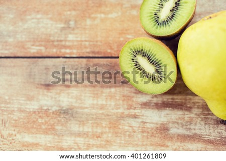 fruits, diet, food and objects concept - close up of ripe kiwi and pear on table - stock photo