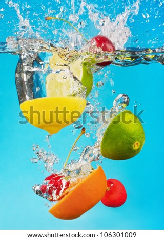 fruits fall deeply under water with a big splash - stock photo
