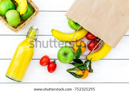 Fruits for picnic. Apple, banana, tangerine on white wooden background top view.