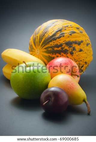 Fruits. Fresh, ripe colorful fruits - plum, pear, apples, bananas and melon arranged on dark background - stock photo