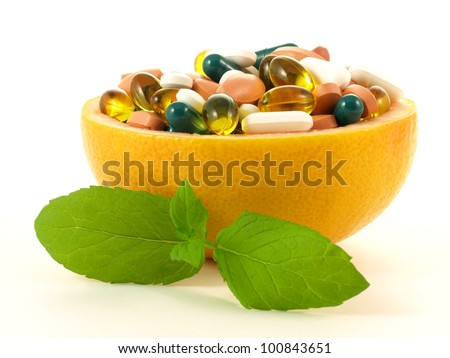 Fruits full of vitamin pills on isolated background. - stock photo