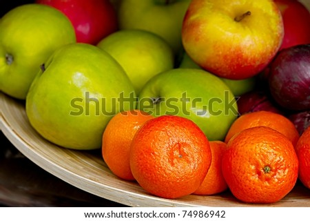 Fruits in a bowl, shallow focus in the front, smooth background