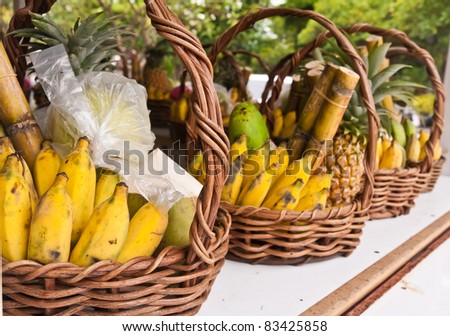 Fruits in basket on shelves included bananas sugarcane and pineapples tilted out - stock photo
