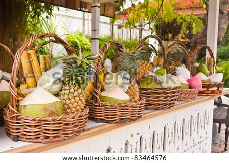 Fruits in basket on shelves included bananas sugarcane coconuts and pineapples tilted right - stock photo