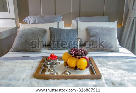 fruits in shiny plate on a wooden tray on bed - stock photo