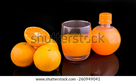 Fruits of a ripe orange and juice in a glass on a black background - stock photo