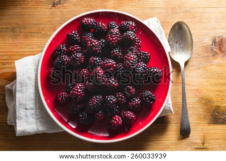 Fruits of the forest:  blackberries. Healthy breakfast food. On red plate against wooden background. - stock photo