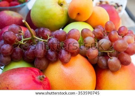Fruits on a plate: grapes, grapefruit, apple, orange, pomegranate, peach - stock photo