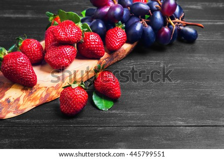 Fruits red and purple, grape varieties Crimson, large strawberries on a board of wood of olive, lime leaves, black on dark wooden background, empty place for text - stock photo
