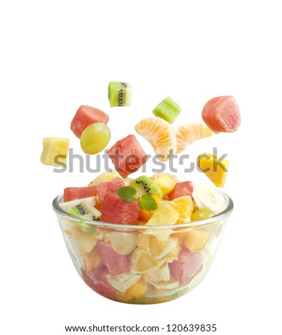 Fruits salad flies to the bowl isolated on white background - stock photo