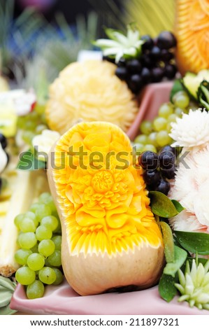 Fruits table with carved pumpkin and grapes  - stock photo