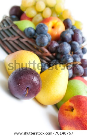 Fruits. Various fresh ripe fruits close-up arranged against a wicker basket full of fruits isolated on white background - stock photo