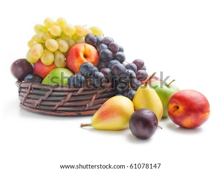 Fruits. Various fresh ripe fruits placed in a wicker basket and around isolated on a white background.