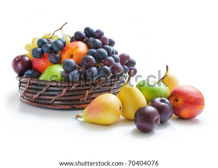 Fruits. Various fresh ripe fruits placed in a wicker basket and around isolated on a white background