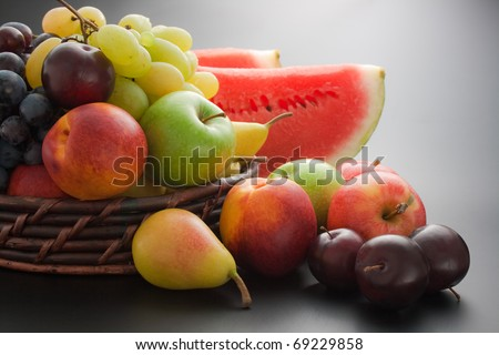 Fruits. Various fresh ripe fruits placed in a wicker basket and around on gray gradient background - stock photo