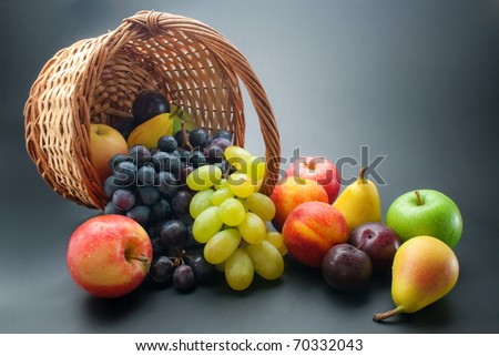 Fruits. Various fresh ripe fruits, scattered from wicker basket on dark gradient background - stock photo