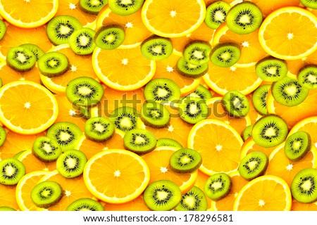 Fruity background set of slices of orange fruit and kiwi. Many slices of kiwi fruit and orange fruit, Fresh kiwis and orange fruit, interesting fruit composition - stock photo
