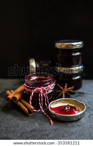 fruity jam and vintage spoons on the old black stone background - stock photo