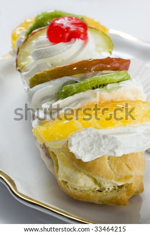 Fruity pastry with fruits and whipped cream. Selective focus on orange - stock photo