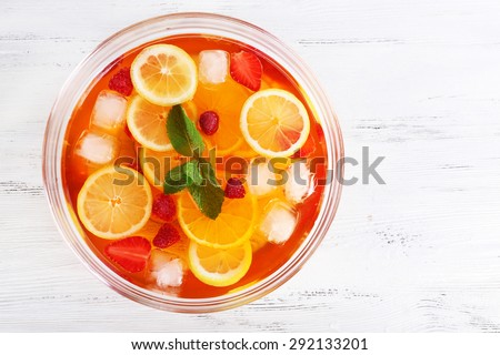 Fruity punch in glass bowl on wooden table, top view - stock photo