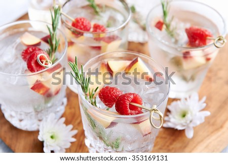 Fruity refreshing mocktails being served on a wooden tray decorated with flowers, raspberries, sliced apples and garnish