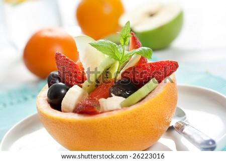 fruity salad in ripe grapefruit. shallow dof - stock photo