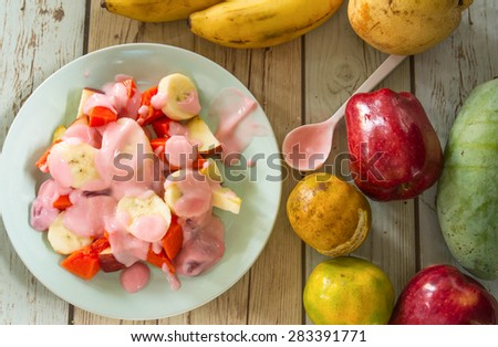 Fruity summer salad in blue bowl with yogurt - stock photo