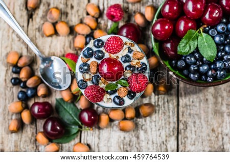 Fruity yogurt ice cream with fruits and hazelnuts in a glass cup, frozen sundae with cherry, raspberry and blueberry, summer dessert, top view - stock photo