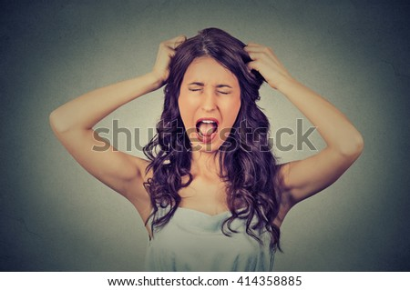Frustrated and angry woman is screaming out loud and pulling her hair isolated on gray wall background  - stock photo