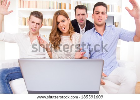 frustrated and shocked casual group of friends sitting on couch looking at laptop, pissed off friends, cheering on computer