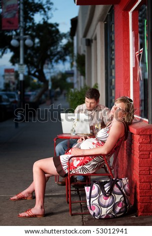 Frustrated and tired pregnant woman resting outside on a chair - stock photo