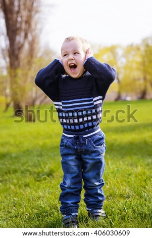 frustrated angry little boy shouts in a spring park - stock photo